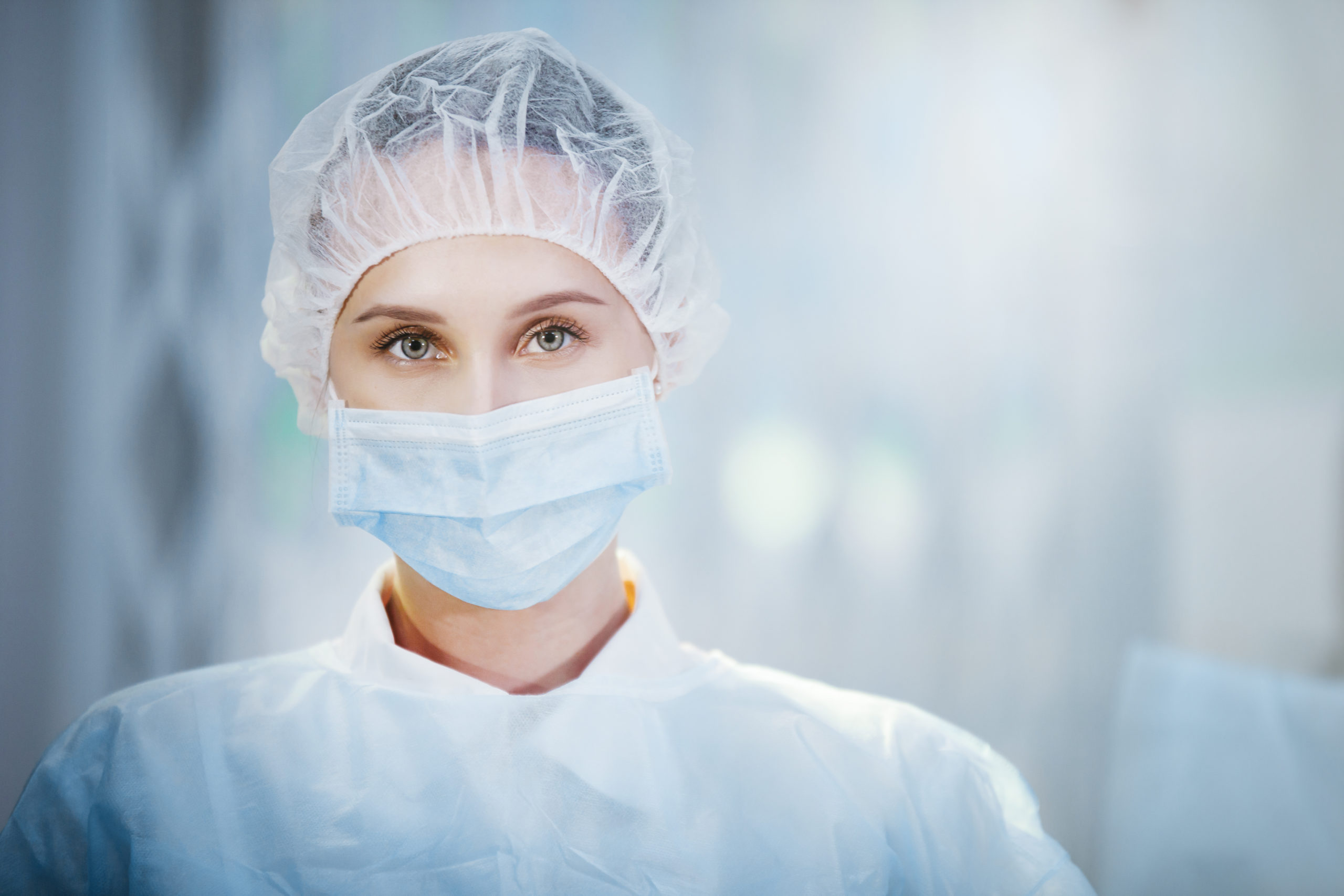 Surgical Nurse in cap and mask in medical clinic. Close-up portrait. Health care, surgery.