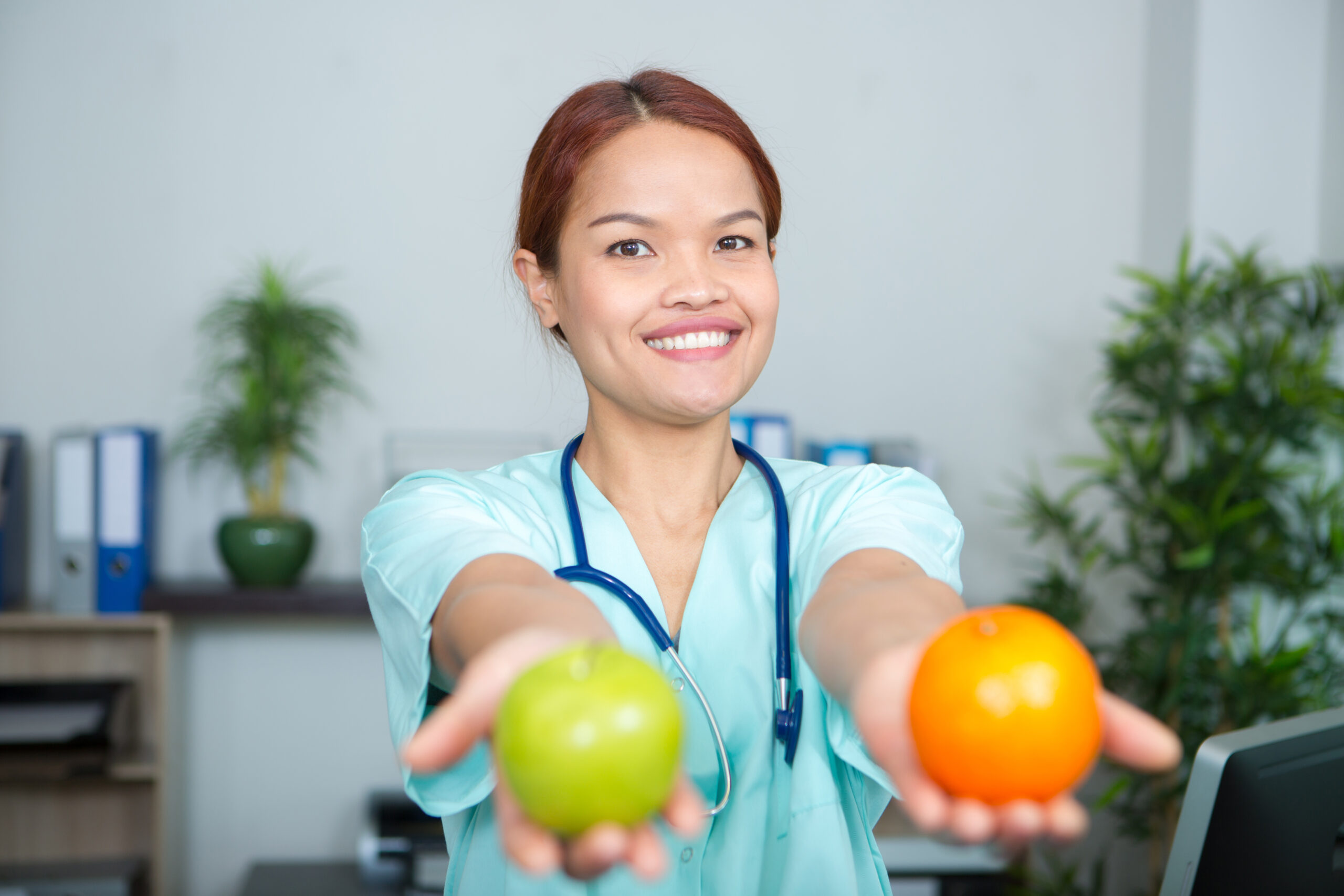 a female doctor holding apple and orange